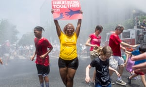 A woman holds a sign while joining others underneath water sprayed from a firetruck to cool people off in Washington DC.