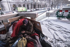 A homeless man tries to keep warm on London's Embankment.