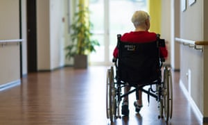 A woman in a wheelchair in a care home.