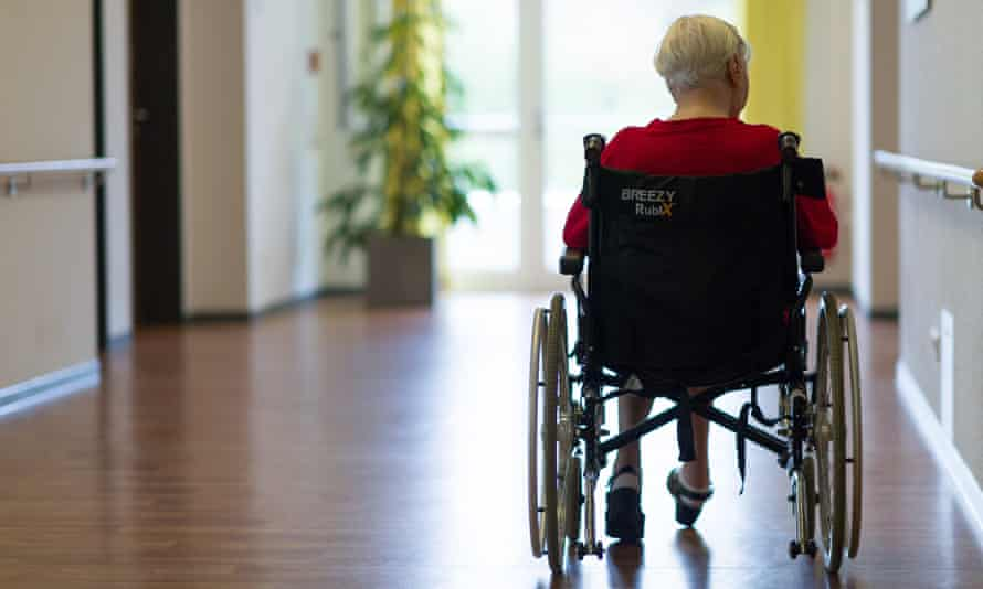 A resident in a wheelchair stands in a hallway of a care home.
