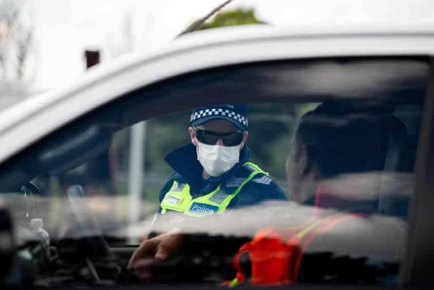 Police are seen checking driver's licenses at a roadblock south of Gisborne.