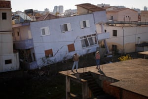 Locals look at a destroyed house after an earthquake hit Durres in Albania, killing at least 21 people.