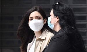 Pedestrians wear face masks