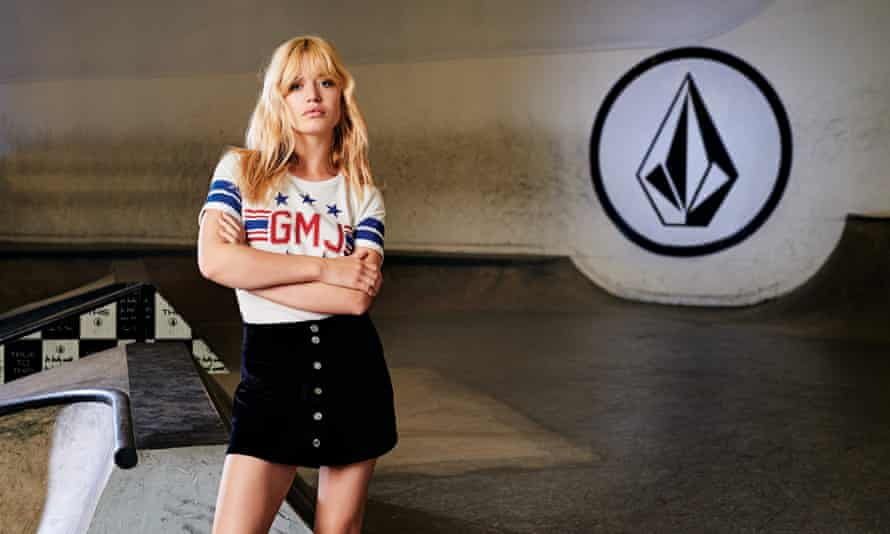 A model wearing a sporty stars and stripes white GMJ T-shirt and black mini-skirt with buttons up the front