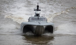 The grey speed boat coming towards the camera