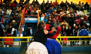 Cholita wrestlers fight it out as the crowd goes wild.