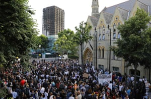 The shell of Grenfell Tower looms over protesters gathering at Notting Hill Methodist Church after marching back from Kensington Town Hall in west London.