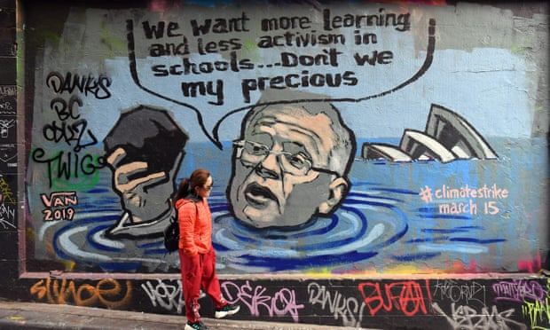 A person walks past a mural showing prime minister Scott Morrison holding a lump of coal