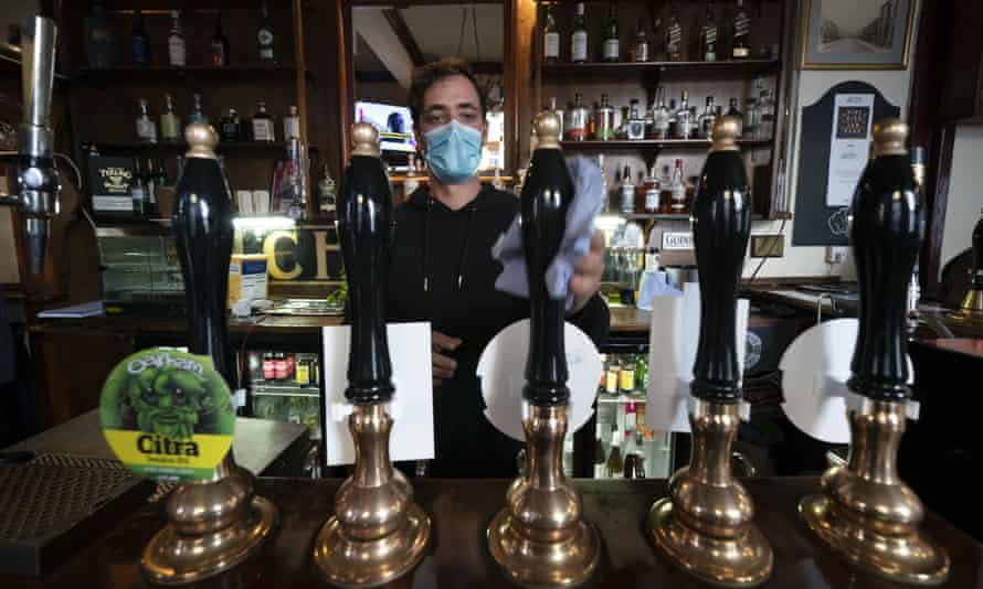 A member of staff cleans beer pumps, at the Dispensary pub in Liverpool