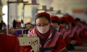 Workers of Songyo Knitwear Factory in Pyongyang produce masks for protection against the new coronavirus.