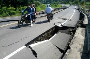Residents ride along a damaged road in Pedernales, Manabi Province,
