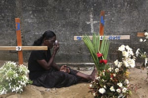 A relative of victims of the Easter bomb blasts wipes away tears while praying at their graves.