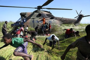 Nhamatanda, Mozambique People run after collecting food aid from a South African National Defence Force (SANDF) helicopter in the aftermath of Cyclone Idai