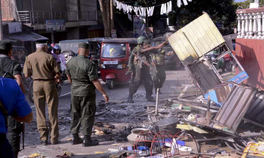 Sri Lanka's army soldiers remove the debris of a vandalized building in Digana, a suburb of Kandy.