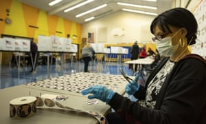 "Election worker Erica Bates cuts up ""I voted"" stickers at Willow School in Lansing, Michigan."