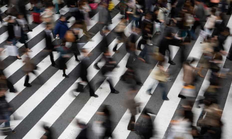 A crowd moves across a pedestrian crossing outside Umeda station, Osaka, Japan