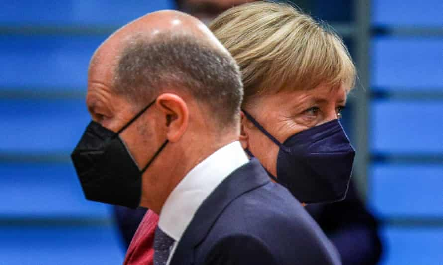 German minister of finance Olaf Scholz crosses paths with Merkel.