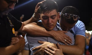 A group of men embrace during a vigil a day after a mass shooting at a Walmart store in El Paso