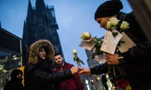 A member of a German-Tunisian association hands out flowers to pedestrians outside the main station in Cologne.