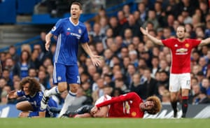 Fellaini holds his knee after the challenge.