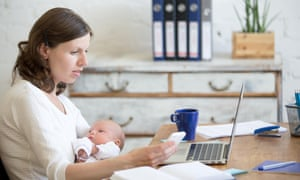 Mum holding her newborn baby while working in home office