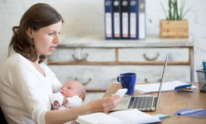 women with baby works from home with laptop and mobile phone