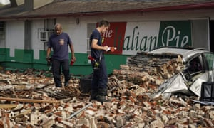 New Orleans firefighters assess damages after a building collapsed from the effects of the hurricane