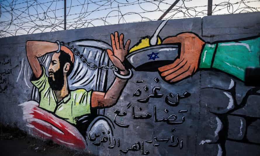A mural depicts Akhras's hunger strike on a wall at Al-Nuseirat refugee camp in the Gaza Strip
