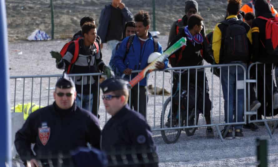Some young migrants wait to leave the Calais camp