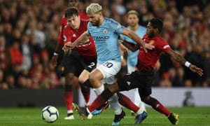 Manchester City striker Sergio Agüero holds off Victor Lindelöf and Fred.
