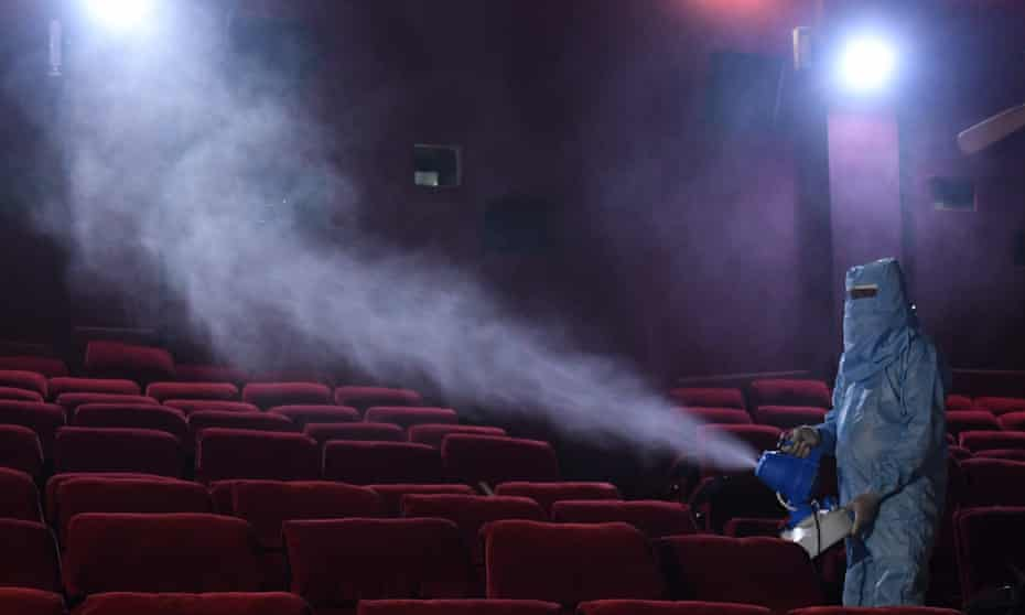 Unprecedented challenges ... a worker disinfects seats at a cinema in Delhi, 13 October.