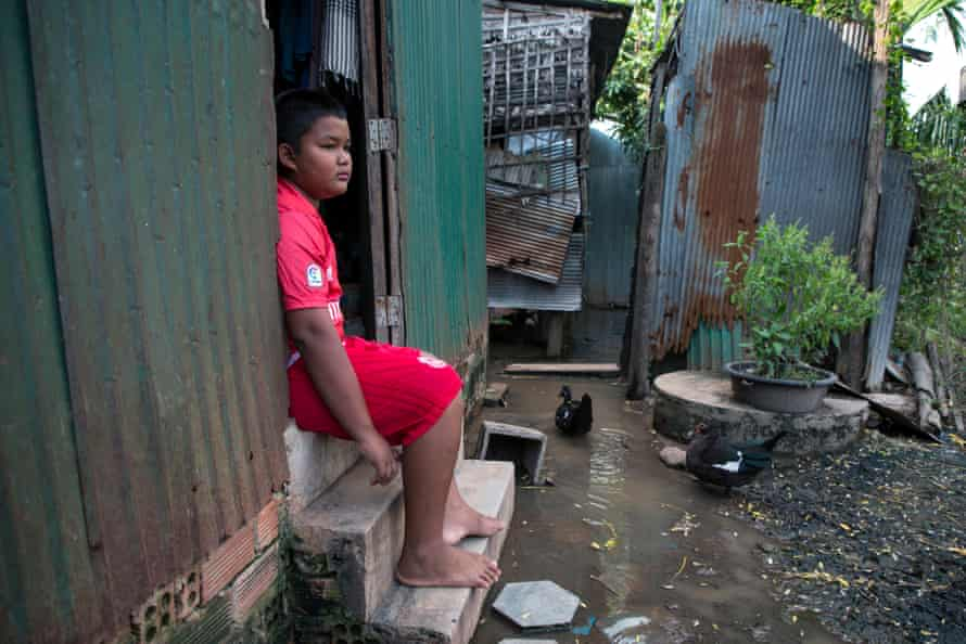 Chan Pheakdey, 10, sits in the doorway of his house.
