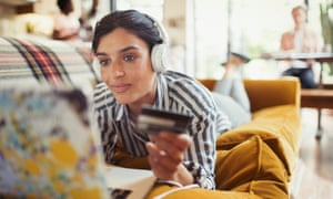 A young woman shops online at home.