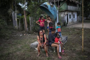 """Women and children congregate around a broken public telephone after a gathering of Tembe tribe members in the Tekohaw village, in Para state, Brazil. """"The Amazon is ending and that's why we're here — so that it doesn't end,"""" said Lorival Tembé, the eldest chieftain, a founder of Tekohaw"""
