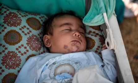 A baby sleeps in a buggy cart along the roadside where thousands of migrants are living without shelter and exposed to the elements near the new temporary camp.