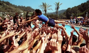 A holiday rep dives into a crowd of people at a pool party for Club 18-30 holidaymakers in Ibiza in 2001.