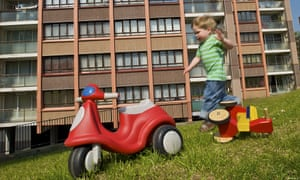 Small boy playing in front of housing estate