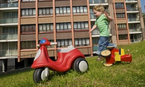 Small boy playing in front of a housing estate