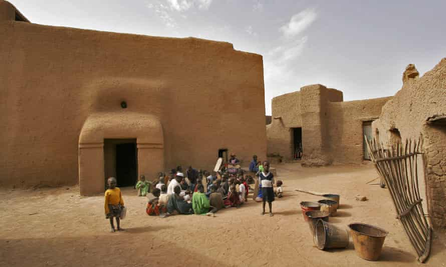 A group of children studying the Koran outside a large earthen mud house, in Djenné.