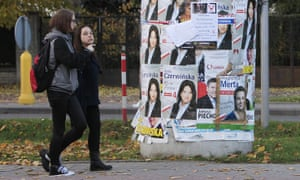 Young people walk past election posters in Łomianki, near Warsaw