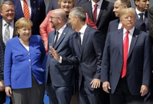 Donald Trump looks up at a helicopter flypast as Angela Merkel chats to Charles Michel and Jens Stoltenberg