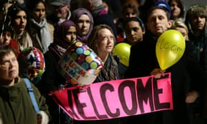 Well-wishers wait to greet the arrival of four Syrian refugees at St Pancras international station