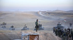 Military vehicles pass by peshmerga soldiers on the route to Mosul