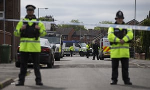 Police officers guard the entrance to a street in Moss Side where raids took place on Sunday.
