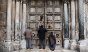 People pray at the closed doors of the Church of the Holy Sepulcher in the Old City of Jerusalem
