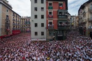 Participants celebrate the Chupinazo (start rocket) to mark the noon kickoff of the San Fermín festival