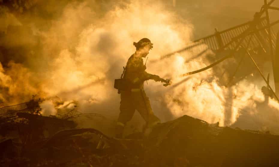 A firefighter sprays down the smoldering remains of a burning home in San Bernardino, California, on Thursday.