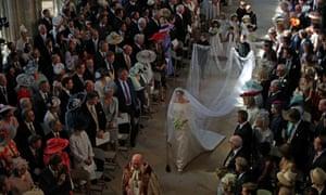 Pageboys carry Markle's veil as she walks down the aisle.