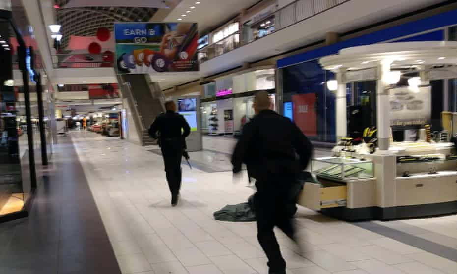 Officers running to the scene of the shooting at the Riverchase Galleria in Birmingham, Alabama, where EJ Bradford, 21, was gunned down by a police officer.