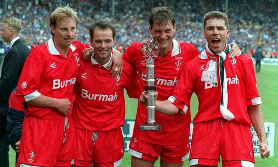Swindon's player-manager, Glenn Hoddle, celebrates alongside three of his teammates following promotion to the top-flight. Hoddle would soon leave to take charge at Chelsea